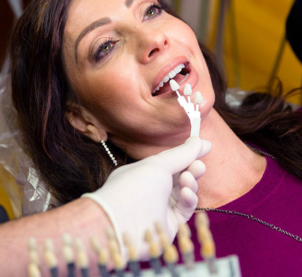 Woman getting dental veneers in dental chair
